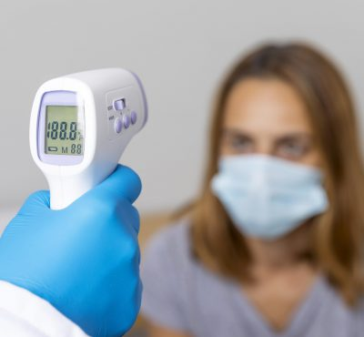 doctor-with-gloves-checking-patient-s-temperature-with-thermometer
